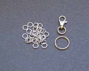 The raw materials - 29 jump rings, a split o-ring, and a trigger snap.